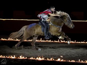 Man in cowboy costume on horseback galloping through flames at Equine Affaire's Fantasia event