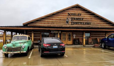 The exterior of Neeley Family Distillery, a wood building on the B-Line Bourbon trail in NKY, with an old bootlegger's car parked out front.