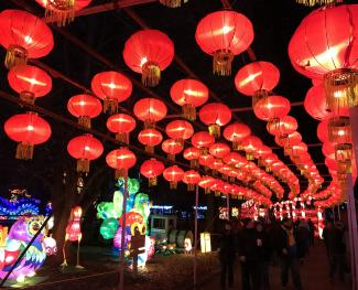 Hundreds of lit, red Chinese paper lanterns with tassels hanging above a crowd of people walking at the Dragon Lights Columbus event.
