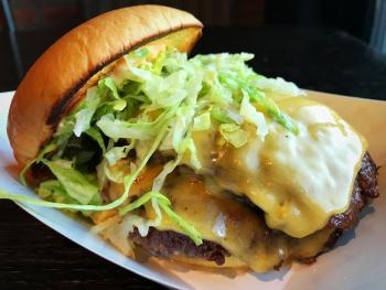 Burger from Preston's Burgers topped with lettuce, cheese, and two patties