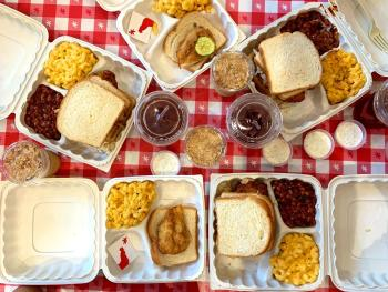 View from above of spread of various boxed meals of chicken wings, toast and mac & cheese at Hot Chicken Takeover