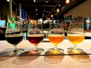 Flight of various beers on bartop counter at Columbus Brewing Company's updated taproom