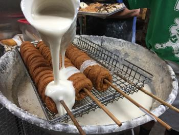Pumpkin donuts being covered in white frosting at Buckeye Donuts