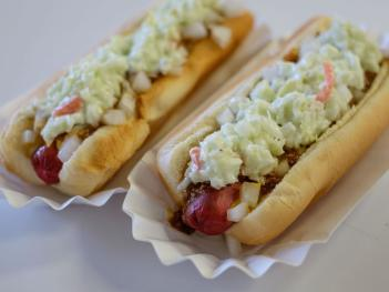 Two hot dogs with potato salad on top from It's a Hot Dog Day