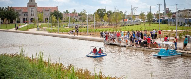 People riding paddle boats in Scissortail Park.