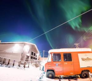 an old beer truck in a parking lot with the Aurora overhead