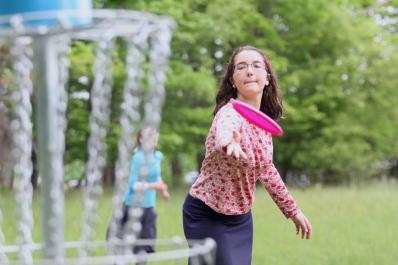 Girl throwing frisby at Jewish Discovery Center