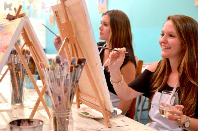 Two girls painting on canvas at Studio 614