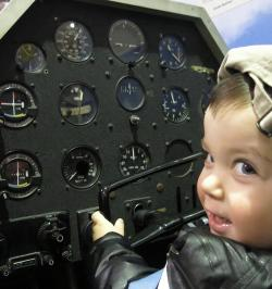 A child pretends to pilot a plane at the Glenn H Curtiss Museum