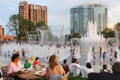 People sitting at restaurant table looking over dozens of children playing in Scioto Mile fountains