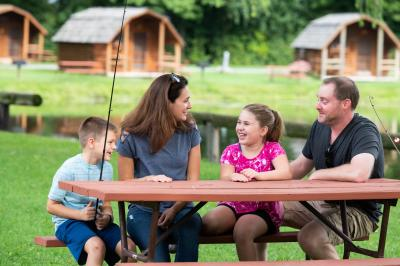 A family smiles around the picnic table at KOA Campgrounds