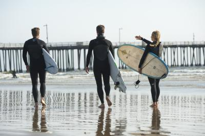 Three surfers walking towards the ocean near a pier in SLO CAL