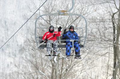 Two skiers wave to the camera while on the chairlift at Bristol Mountain