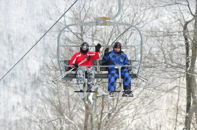 Two people waving from the chairlift at Bristol Mountain Ski Resort