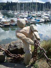 stone statue of man pulling chain at the marina