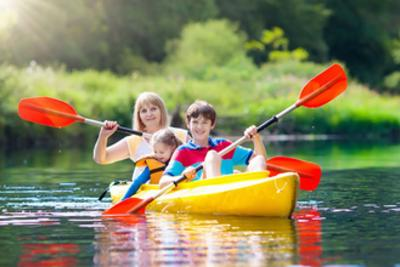 Kids gliding across the water in a kayak