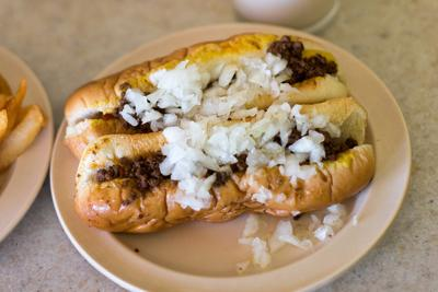 Two hot weiners from Olneyville New York System on a plate with onions on top