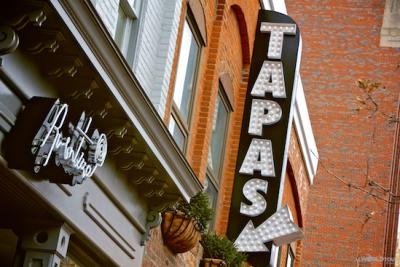"""A sign for Aventura restaurant and another sign that reads """"Tapas"""" in big letters with an arrow pointing to the Aventura sign."""