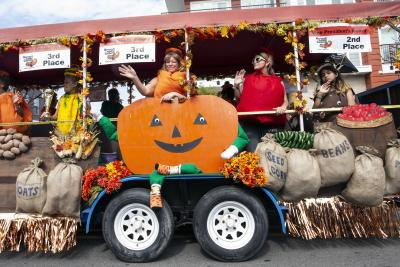 Women and girls dressed as a pumpkin, tomato, corn and potato on a float