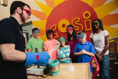 Scientist with gloves and tongs performing chemistry experiments for children at COSI