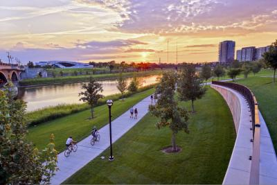 Aerial view of people riding bikes on path along river during sunset at the Scioto Mile