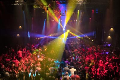 View of crowd under colorful disco lights in front of stage during the Party With the Pros Arnold Sports Festival after-party