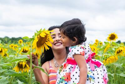 A child looks at a sunflower while her mom holds her up