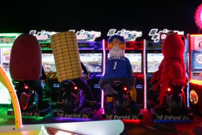 Four mascots sit in front of screens in an arcade.