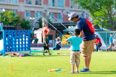 "Father and son enjoying lawn fishing at Summer Family ""Camp Out"" in Sugar Land Town Square"