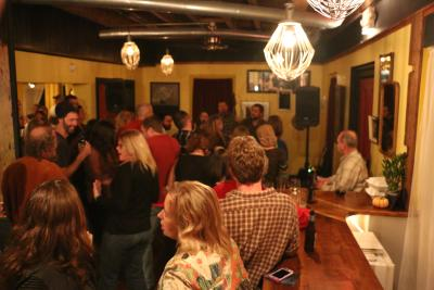 A crowd enjoys live music and dancing inside of Roots cafe during the night