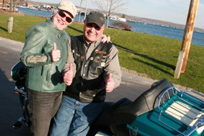 Two men pose with a thumbs up in front of their motorcycles