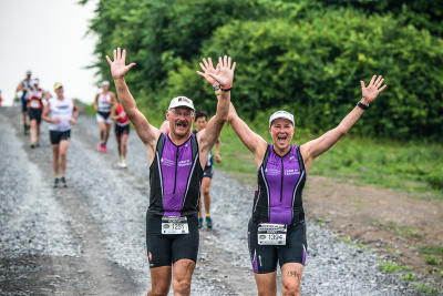 Runners cross the finish line with smiling faces at the Mussle man triathalon