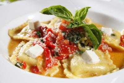 Bowl of ravioli topped with red tomatos, cheese, and herbs from Due Amici