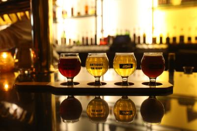 Flight of colorful sour beers on bar in dimly-lit Antiques on High