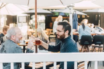 Two men raising their glasses to each other at an outdoor eating venue in SLO CAL
