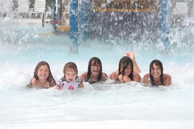 A group of kids pose while getting water dumped on them inside of Roseland Waterpark