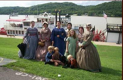 Women in nineteeth century dresses in front of a paddlewheeler on the Ohio river