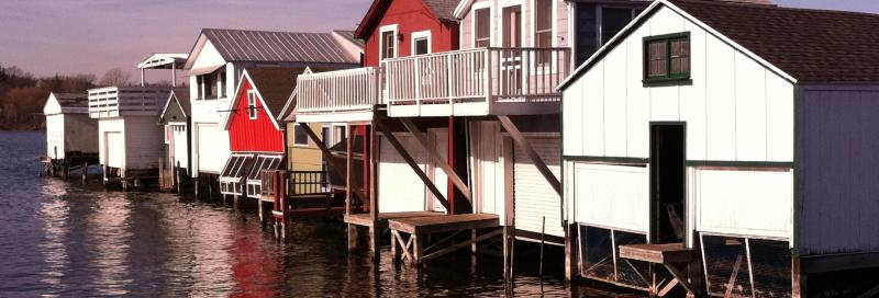 Boat houses sit on canandaigua pier on a sunny day