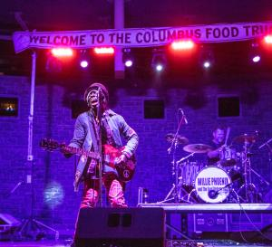 Willie Phoenix playing guitar and singing into microphone on stage at night during the Columbus Food Truck Festival