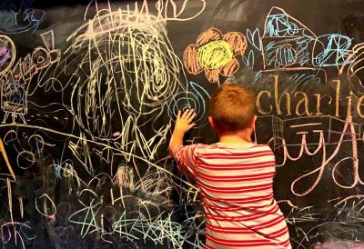 Young child drawing on chalkboard wall