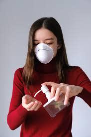 Woman wearing facemask applying hand sanitizer