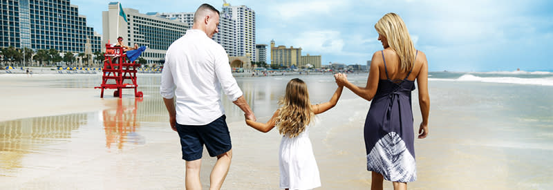 A family holds hands while walking on Daytona Beach near a lifeguard stand.