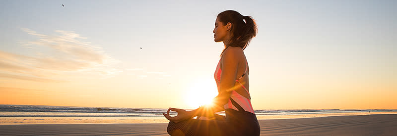 A woman sits in a yogic lotus position on Daytona Beach at sunrise.
