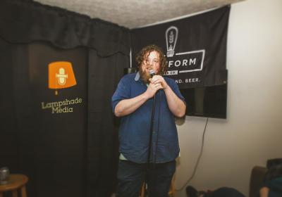Lampshade Media manager Mel Millimen performing stand-up comedy during a Lampshade event