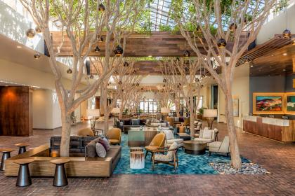 Atrium ficus tree-lined lobby at the Portola Hotel and Spa. Lounge area with blue carpet and many types of chairs.