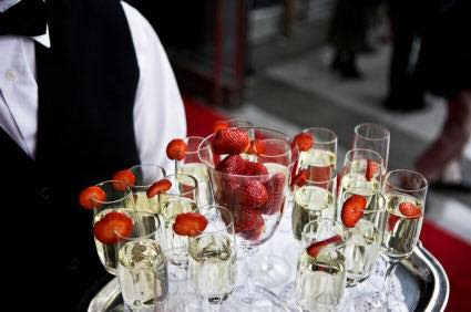 Caterer holding tray of champagne with strawberries
