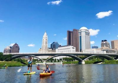 Kayakers in Scioto River with Scioto Mile and city skyline in background under blue sky
