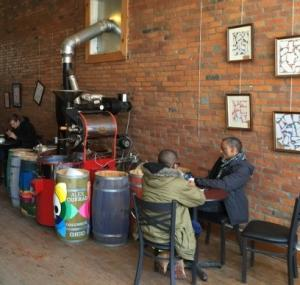 Two people enjoying coffee next to giant coffeemakin apparatus, brick walls lined with artwork inside Upper Cup Coffee