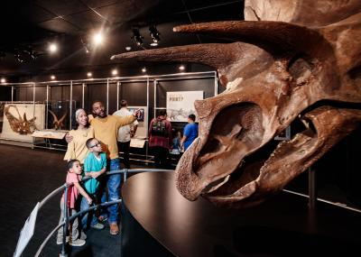 Family with children admiring Triceratops dinosaur skeleton at COSI