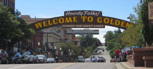 Golden welcome sign and downtown street